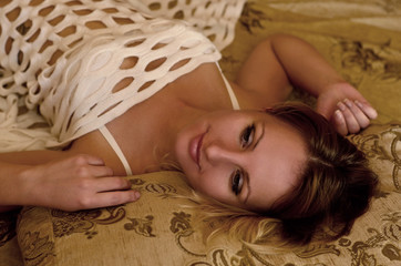 Young and beautiful caucasian girl in white underwear lying on a bed with beige bedding.