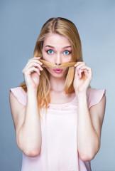 Portrait d'une jeune femme étonnée, les cheveux devant la bouche