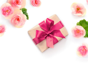 Gift box with red ribbon and bow on white with flowers background. flat lat, top view