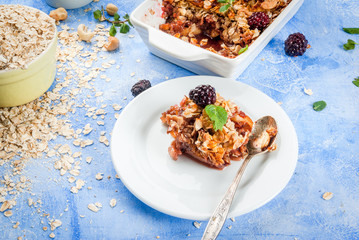 Freshly baked diet berry crumble with oatmeal with fresh berries blackberries decorated with mint leaves. In a frying pan for baking and in plate, on blue stone concrete table copy space
