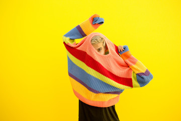 Man peeking out of sweater on yellow background