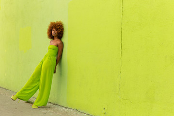 Woman wearing lime green jumpsuit leaning against wall