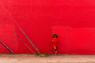Woman in red dress leaning against red wall reading a book