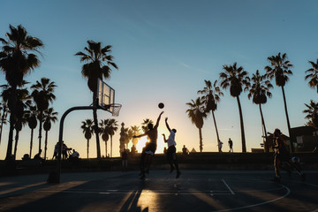 Friends playing basketball at sunset