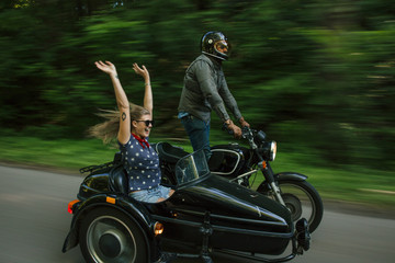 Blurred motion image of couple riding motorbike with sidecare