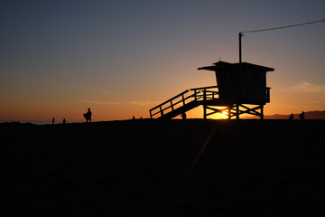 Silhouette of lifeguard tower and people on beach at sunset