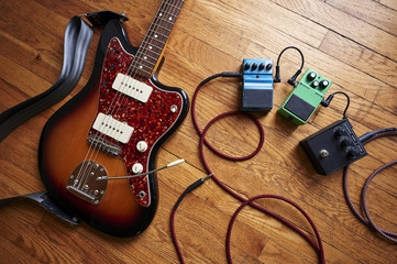 an electric guitar with cables and pedals
