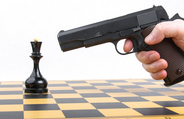 hand with gun took aim at chess piece