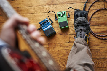 a person playing a guitar and using effect pedals