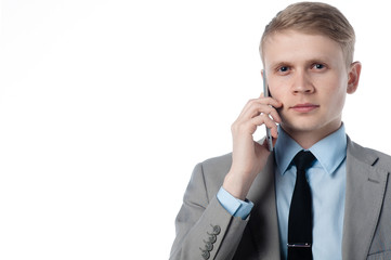 young businessman talking on the phone and looks at you. in a business suit on a white background.
