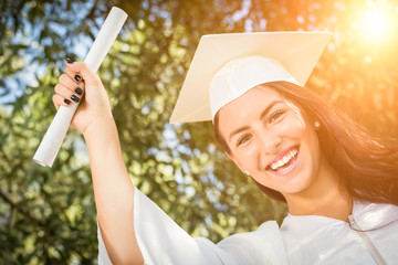 Attractive Mixed Race Girl Celebrating Her Graduation Outside In Cap and Gown with Diploma in Hand.