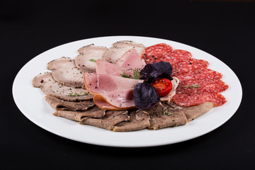 meat delicatessen plate arranged with cherry tomato, pepper and bazil. ham assortment on black background