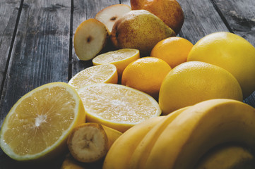 Bunch of fresh yellow fruit on an old wooden table. Selective focus and small depth of field.