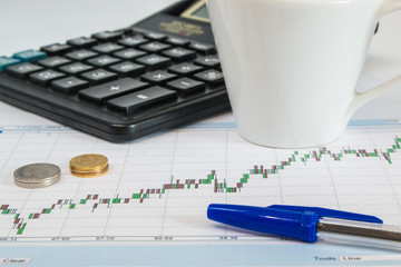 Business graph on a white background with calculator, cup of coffee, pen and money