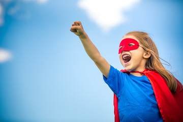 Funny little girl plaing power super hero over blue sky background. Superhero concept.