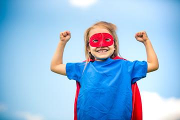Funny little girl plaing power super hero over blue sky background. Superhero concept.