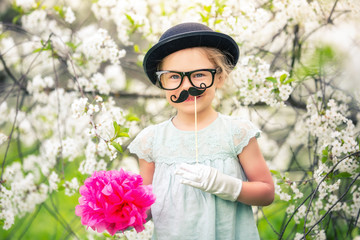 Funny girl in hat, glasses and gloves and with fake mustache playing in spring garden.