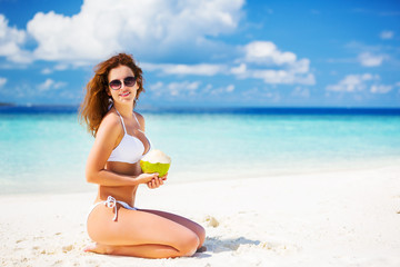 Young woman in bikini sitting on the beach