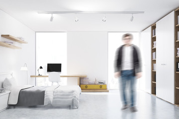 Man in a white walled bedroom with study corner