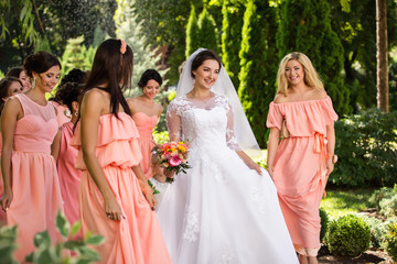 Beautiful bride and her friends- bridesmaids having fun and walking in park after wedding ceremony