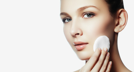 Beautiful brunette woman removing makeup from her face, skin care concept. Beauty fresh girl cleaning face with cotton swab. Beautiful young woman cleaning her face with cotton