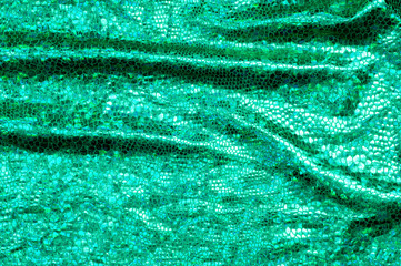 texture of silk fabric; background. green skin of the snake. shiny fabric