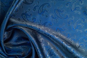 The texture of the silk fabric. Dark blue. With a picture of cucumbers
