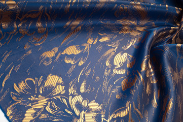 Fabric texture of silk with gold-painted flowers