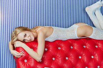young charming girl in sexy costume posing on the back of the red sofa