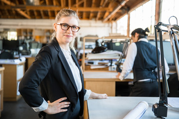 Young designer business woman stands confidently at work active cheerful and positive