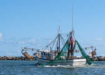 Shrimp fishing boat sailing on water out to the Gulf of Mexico in Florida