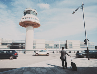 Silhouette of businessman with luggage standing near airport in front of air traffic control tower car and parking, experienced male employer with suitcase waiting for taxi outdoors after work travel