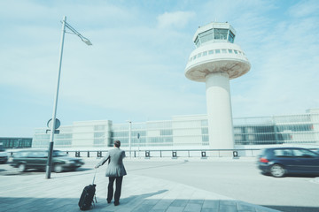 Rear view of man with luggage standing in front of air traffic control tower near airport parking, experienced male employer with suitcase waiting for taxi outdoors near airport terminal in Barcelona