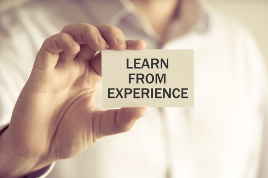 Businessman holding LEARN FROM EXPERIENCE message card