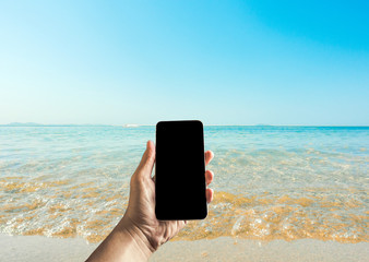 technology, travel, tourism, communication and people concept - close up of male hand holding showing smartphone on summer beach with black screens display background