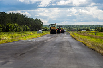 Brigade road workers laying asphalt on the road in the summer with the help of special equipment asphalt paver
