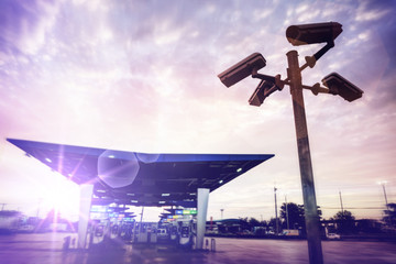 Closed circuit television camera at gas station in sunset sky.