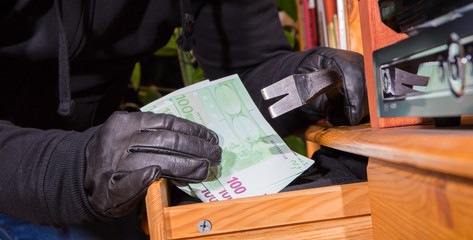 ein Einbrecher entwendet Geldscheine aus einer geöffneten Schublade