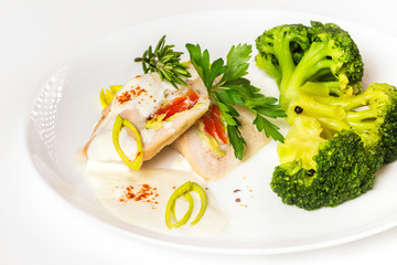 Plate of steamed chicken and broccoli with white sauce isolated.