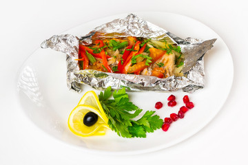 White fish fillet baked in foil with vegetables on a plate at isolated background.