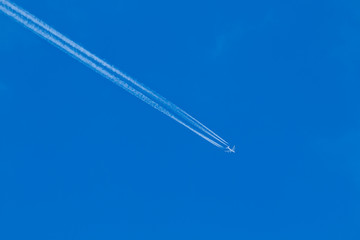 Airplane leaves a jet stream across a clear blue sky.