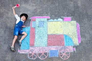 little kid boy having fun with train chalks picture