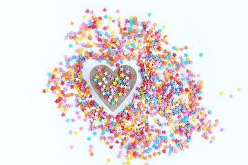 bright colored confectionery sprinkling of stars and wooden heart on a light background, soft focus, blur.