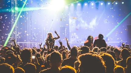 Young people dancing at night club - Hands up and multicolored confetti at nightclub after party -...