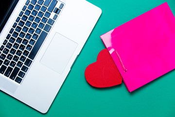 beautiful heart shaped toy, pink shopping bag and modern silver laptop on the wonderful blue background