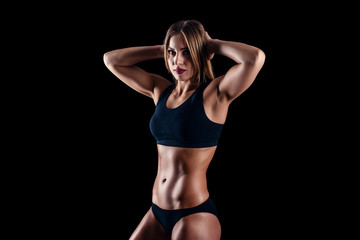 Sporty young girl in sportswear exercising on black background. Tanned young athletic woman. A great sport female body.
