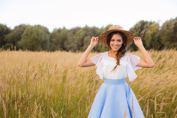 Girl with circlet of flowers walking in golden dried grass field