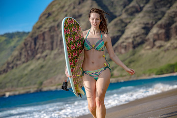 surfing girl with surboard on a sandy beach