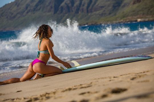 Surfer girl with surfboard on sandy beach