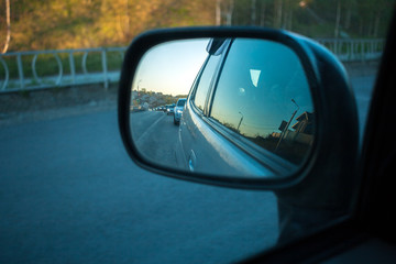 Row of cars on road is visible in side-view mirror of car in summer evening.